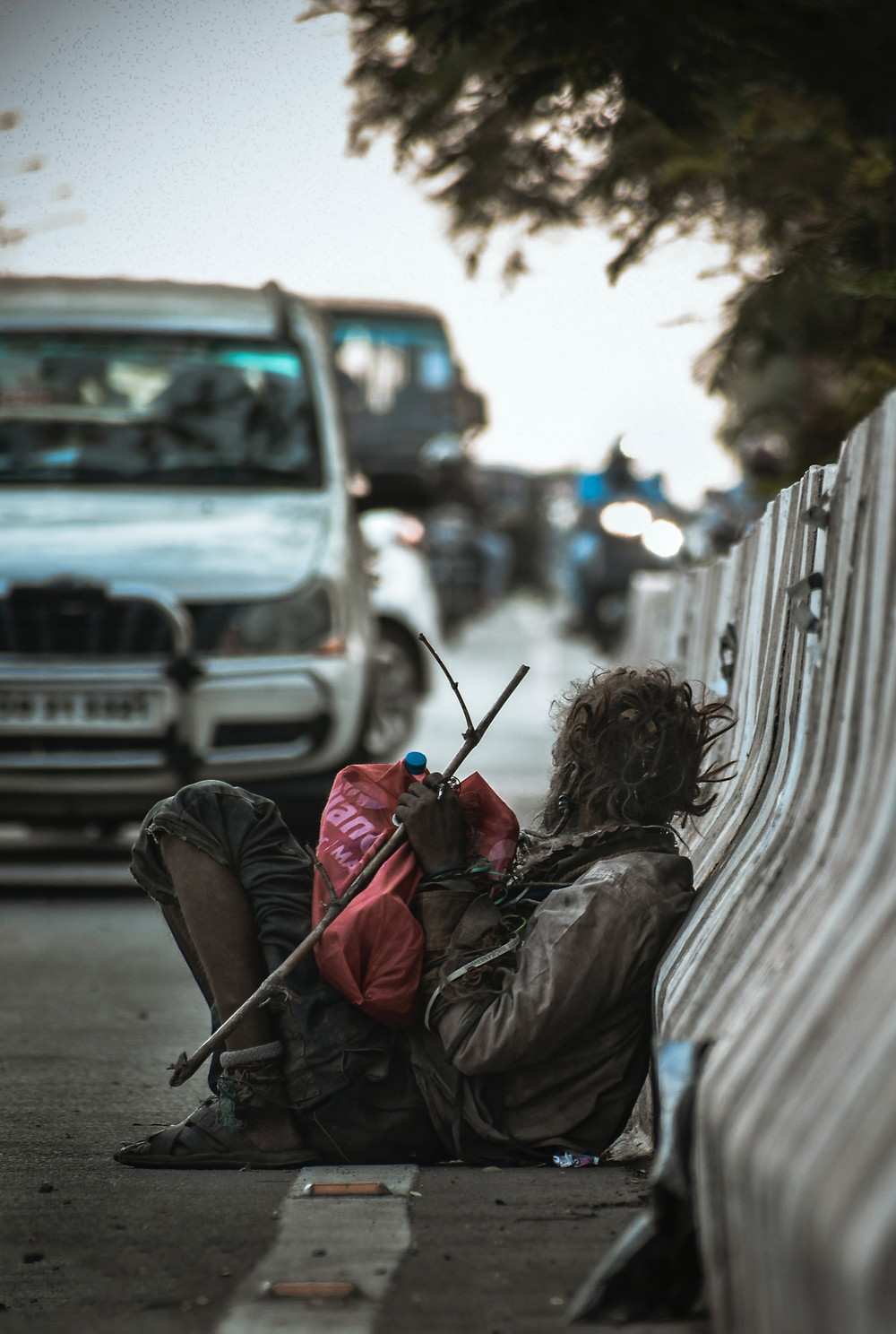Homeless man leaning up against the side of the road
