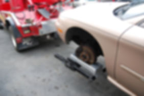 Car missing wheel on Collins Tow Cradles with tow truck wheel lift