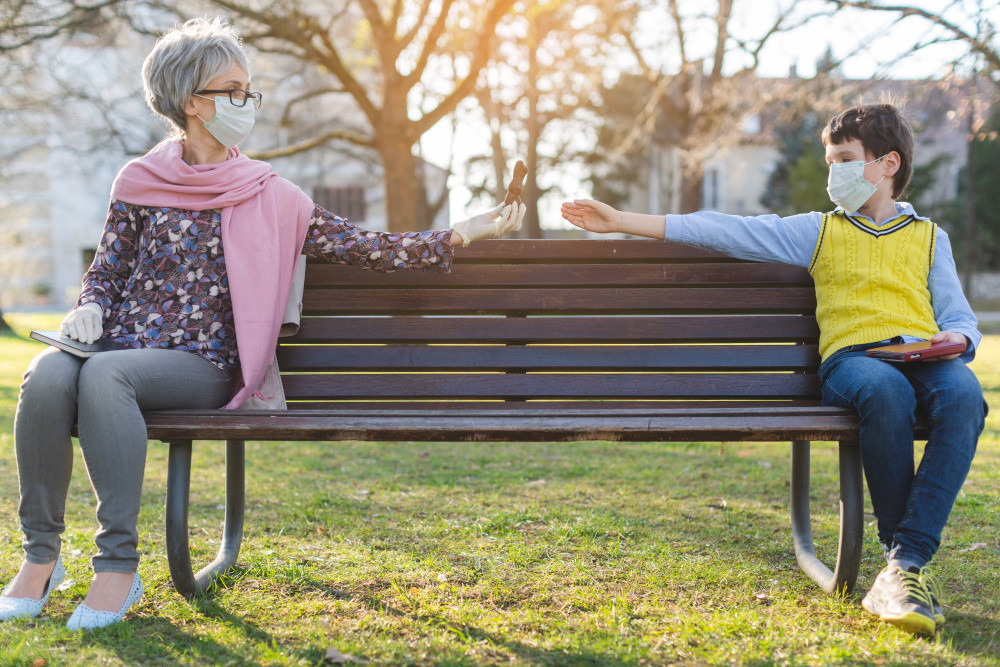 grandmother and grandson wearing masks sitting apart on a bench
