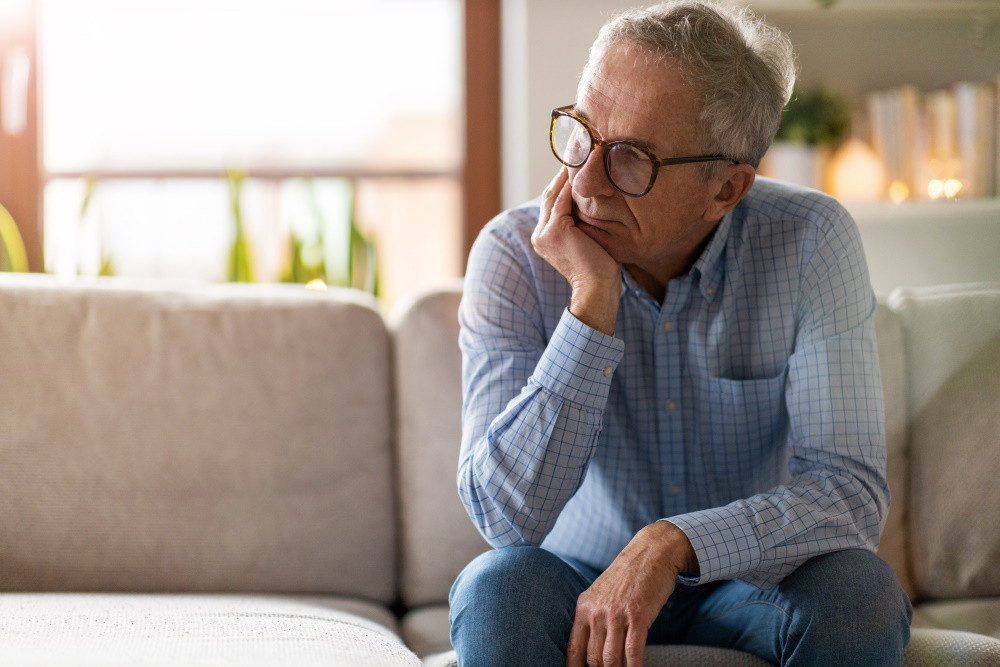 older man sitting on couch at home
