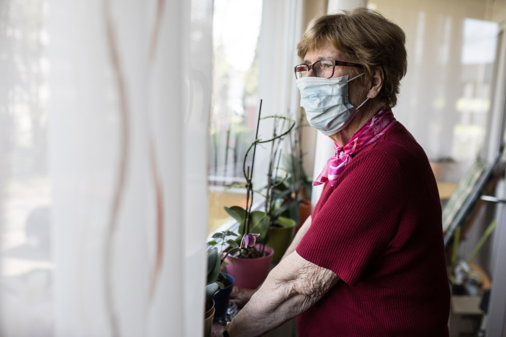 senior woman in mask looking out window