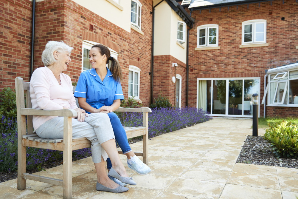 assisted living facility resident sitting on bench with staff member