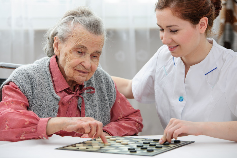 senior woman playing checkers with assisted living nurse