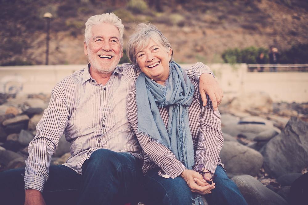happy older couple sitting outside