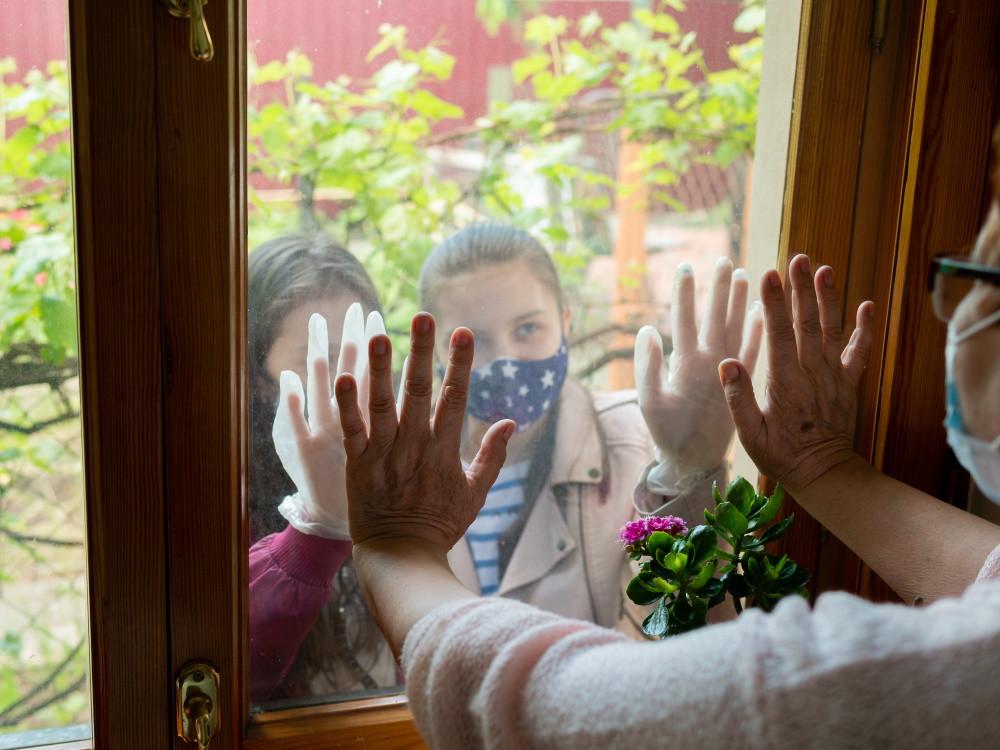 Senior looking through window at grandchildren wearing masks