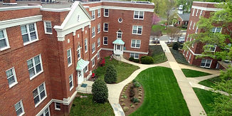 Birdseye view of Lyon Village Apartments. Classic red brick archictecture with a large lush courtyard between buildings.