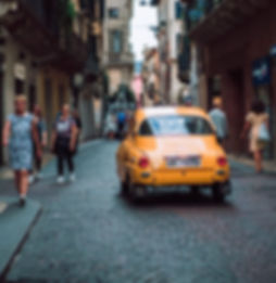 A car driving through an old town on our escorted tours