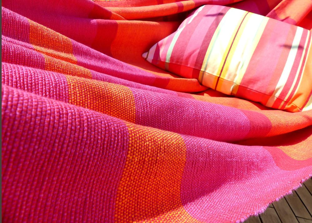Notre hamac double PASSION rouge en coton extra doux est assemblé avec un coussin en bayadère