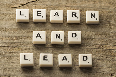 Learn and Lead text on a wooden background.jpg