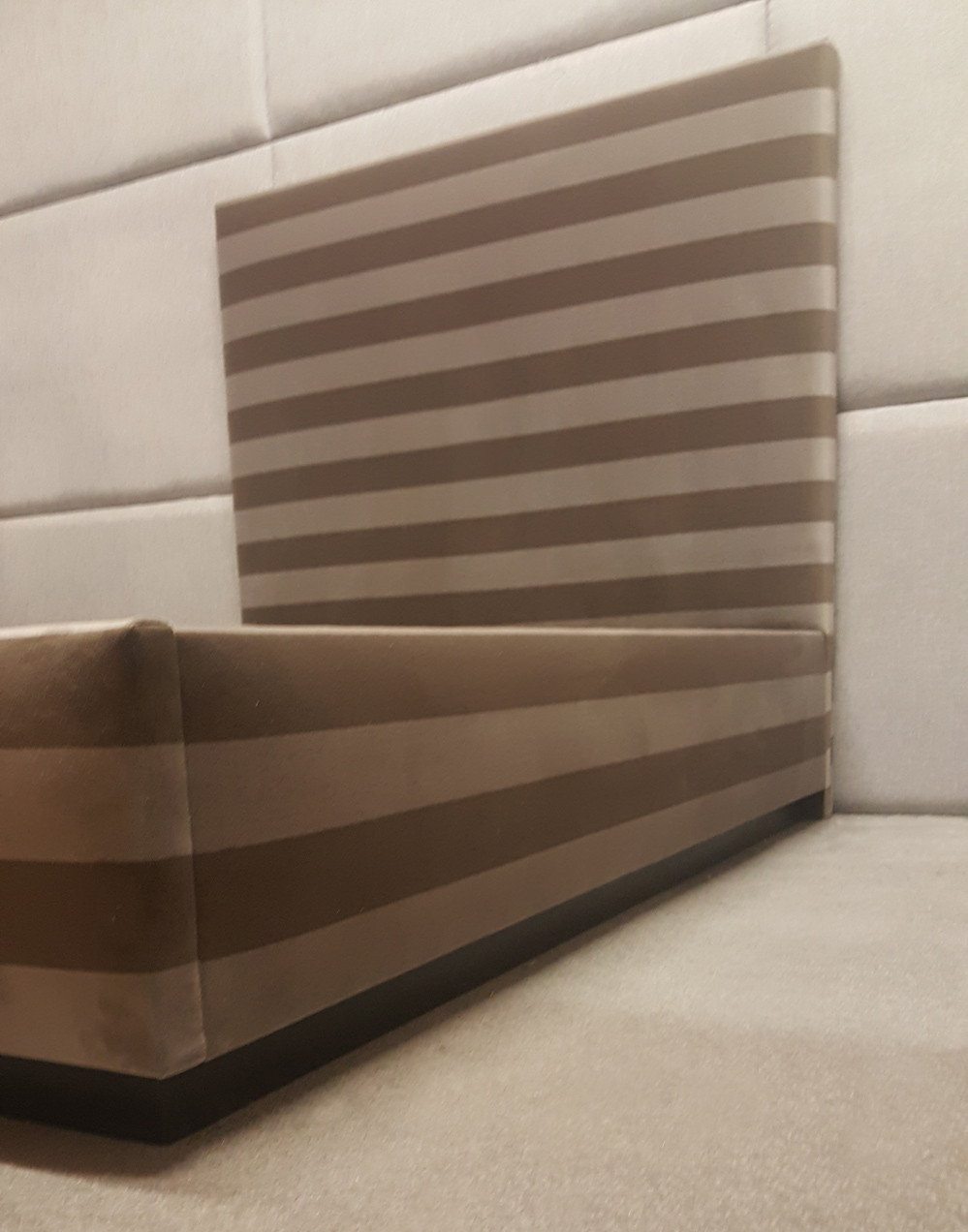Striped fabric on a simple headboard and bed frame