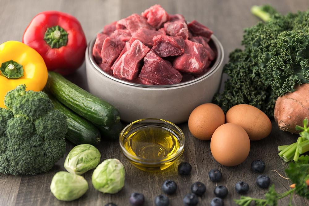 Carne, uova, olio, verdure in una ciotola e su un tavolo
