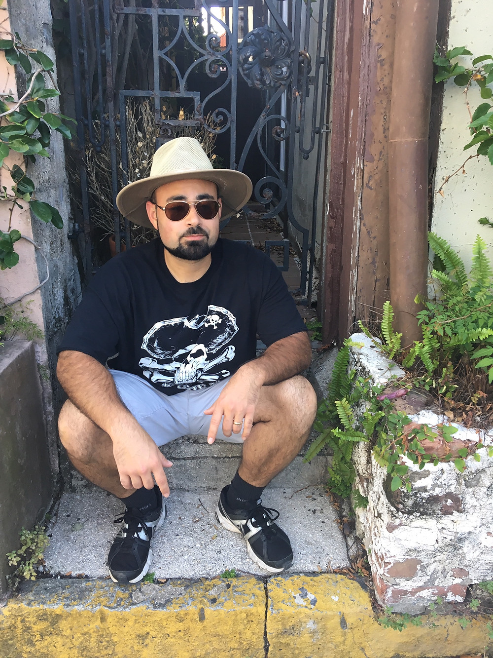 man sitting on stone step on vacation wearing wide-brimmed hat and sunglasses