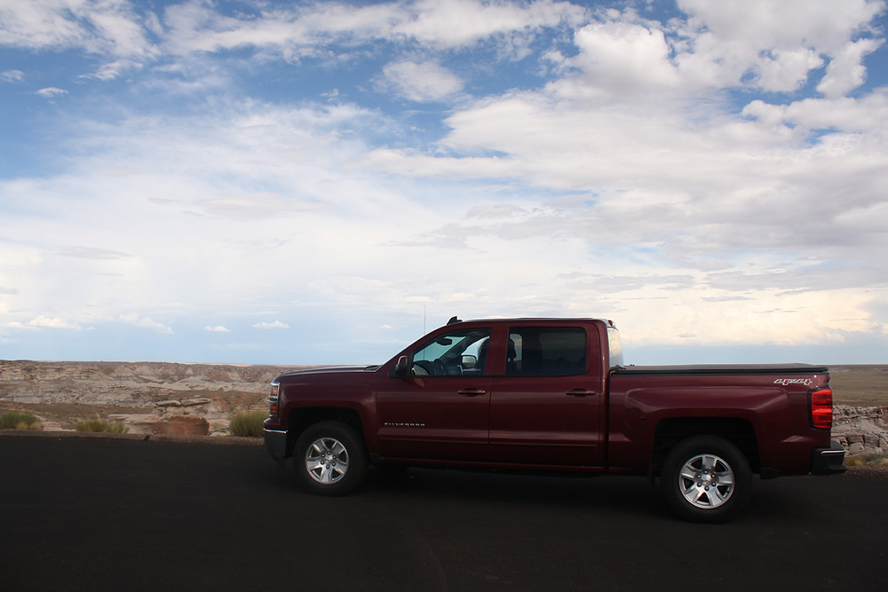 red Chevy Silverado truck on black road overlooking blue sky