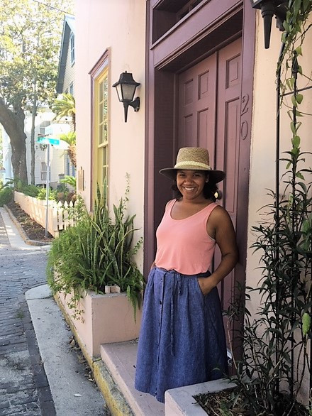 woman with hat stands in front of door on cobbled street in downtown St. Augustine