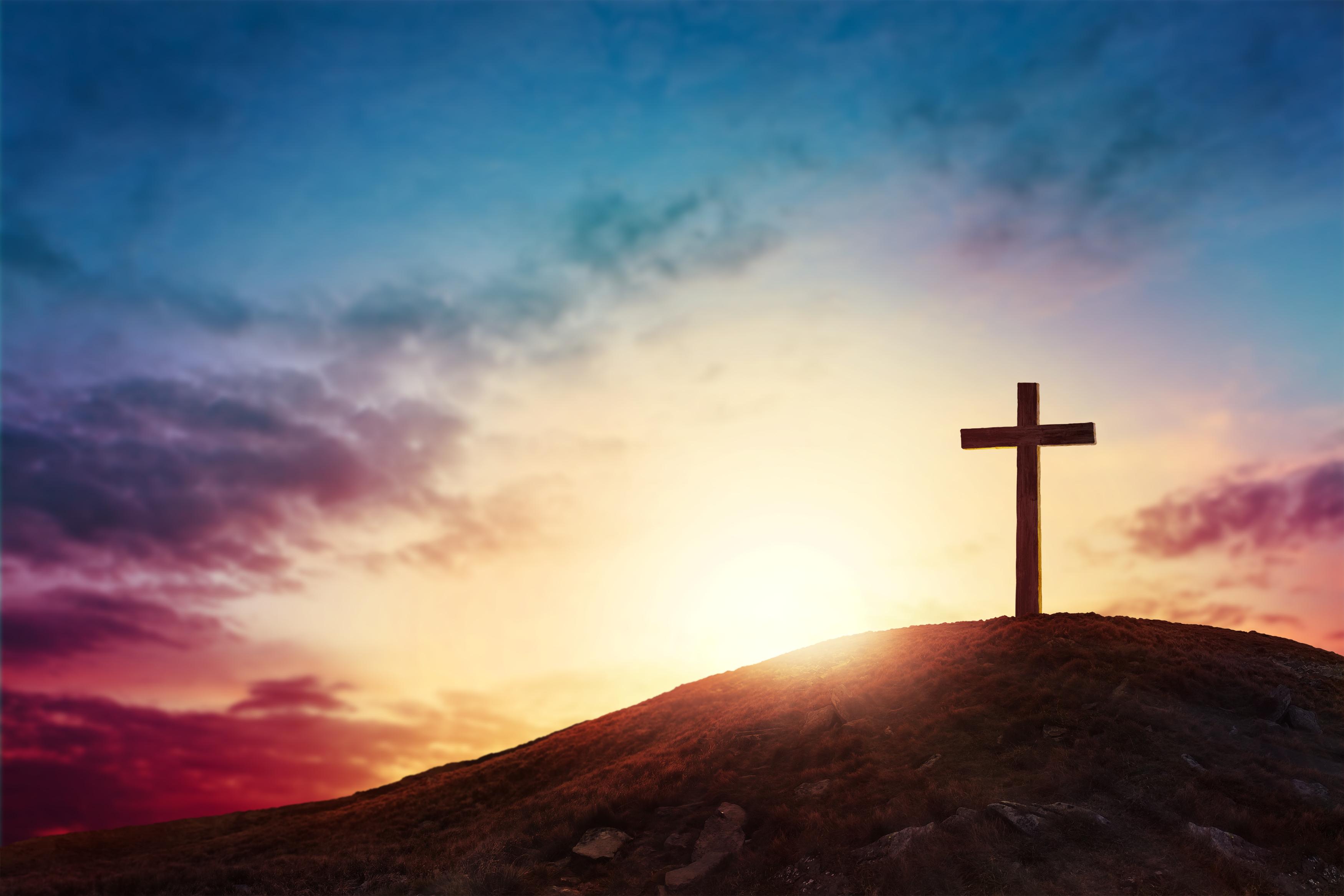 Silhouette cross on Calvary mountain sun