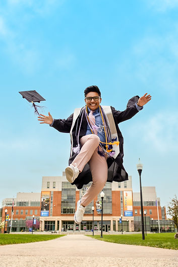A guy in a graduation gown jumping into the air in front of Southern Connecticut State University.