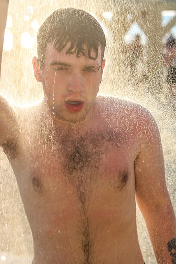 A shirtless young man showering on the beach as the sun sets.