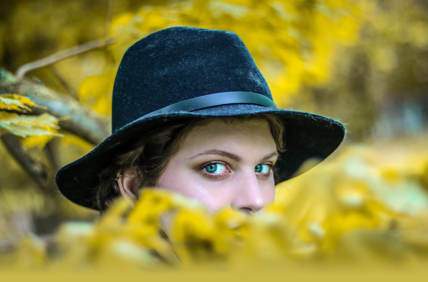 A woman with blue eyes and a black hat, peering over yellow leaves.