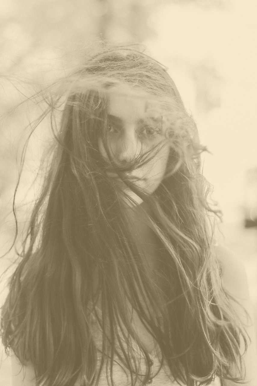 A girl with dark hair blowing in front of her face