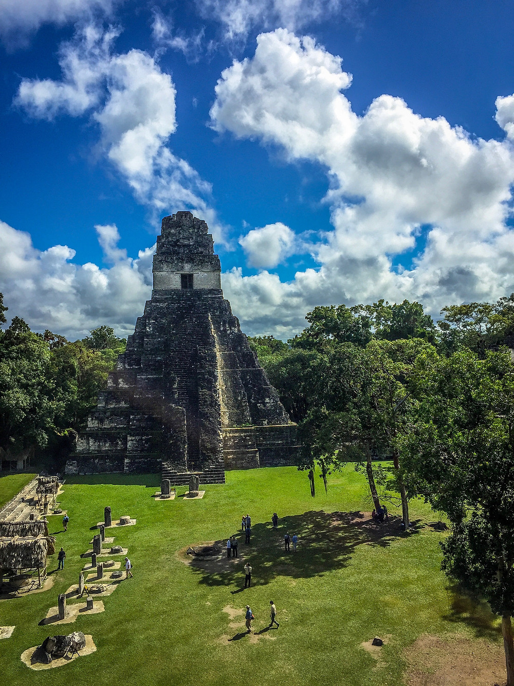 Stunning photo of Tikal ruins with white clouds in the background