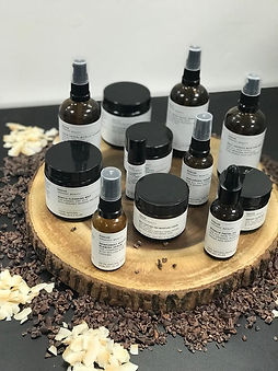 Evolve beauty organic skincare products laid out on a wooden mat on a dark table.