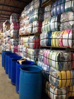 100 Pound Bales of used clothing stacked on wood pallets ready to be shipped all around the world