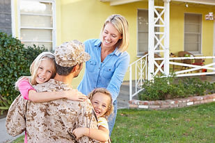 Family Welcoming Husband Home On Army Le