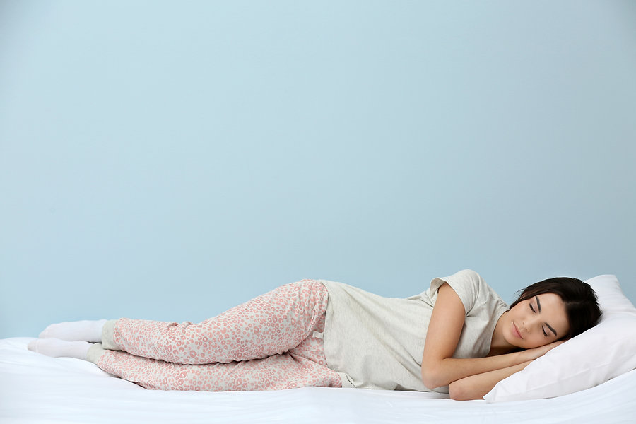 Young woman in pajamas sleeping on bed o