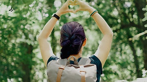 Girl in a forest making heart shape with hands