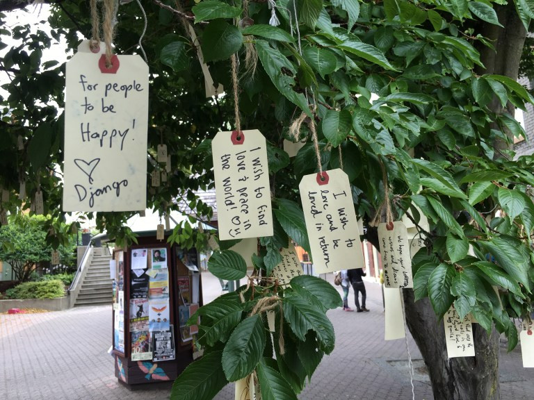 "A tree with little notes on luggage tags hanging from the leaves. The first note says ""For people to be happy"", the second note says ""I wish to find love"""