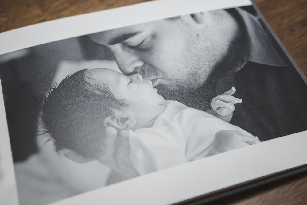 Andria Grodzinsky Photography Newborn photo album showing a black and white photo of a dad kissing his baby