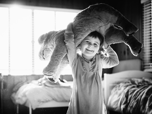Andria Grodzinsky black and white of a little girl holding a stuffed animal over her head