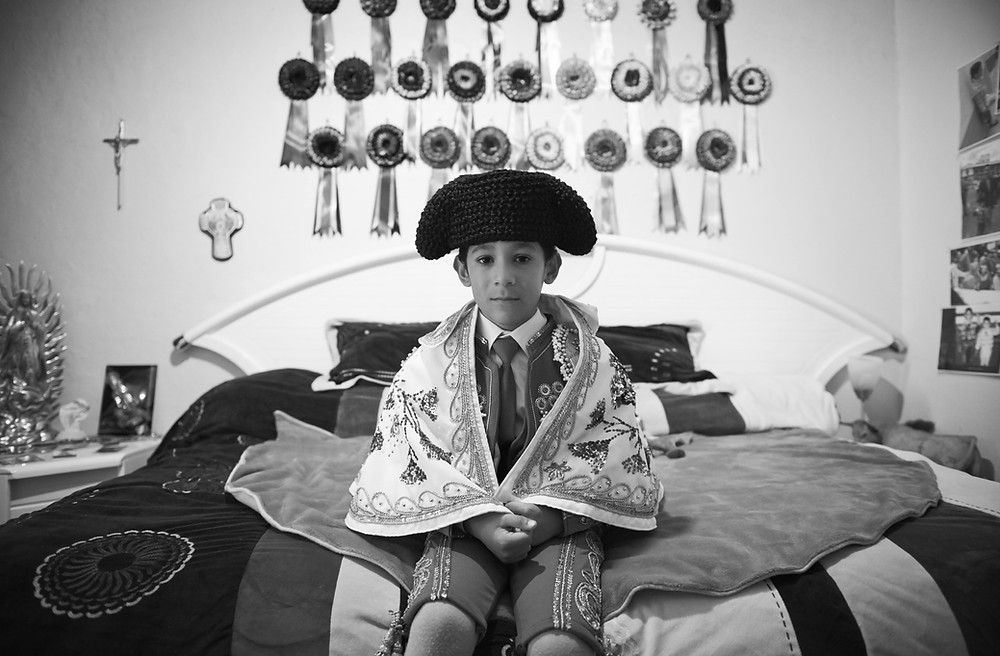 Salvador, aged 6, sits on his bed in anticipation of witnessing the afternoon bullfight at Plaza de Toros Mexico. Behind him are several ribbons, each symbolizing a bull dedicated to him by his matador heroes. Salvador's family is wealthy and are staunch Catholics. They believe God will protect him from any harm. From the series 'Little Bullfighters' a personal project. Shot in December 2015.