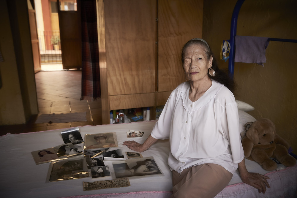 Sixty-nine year old Patricia poses proudly with photos from her days as a Pin-up model. She has lost the ability to hear, speak and see out of one eye due to beatings she sustained.  Patricia resides in Casa Xochiquetzal, a retirement home in a dilapidated Spanish casona in one of Mexico City's roughest barrios.  The Casa is named after the Aztec goddess of sex and love and its residents are retired sex workers.  From the series 'Casa Xochiquetzal', a personal project. Shot in Mexico City, June 2017.