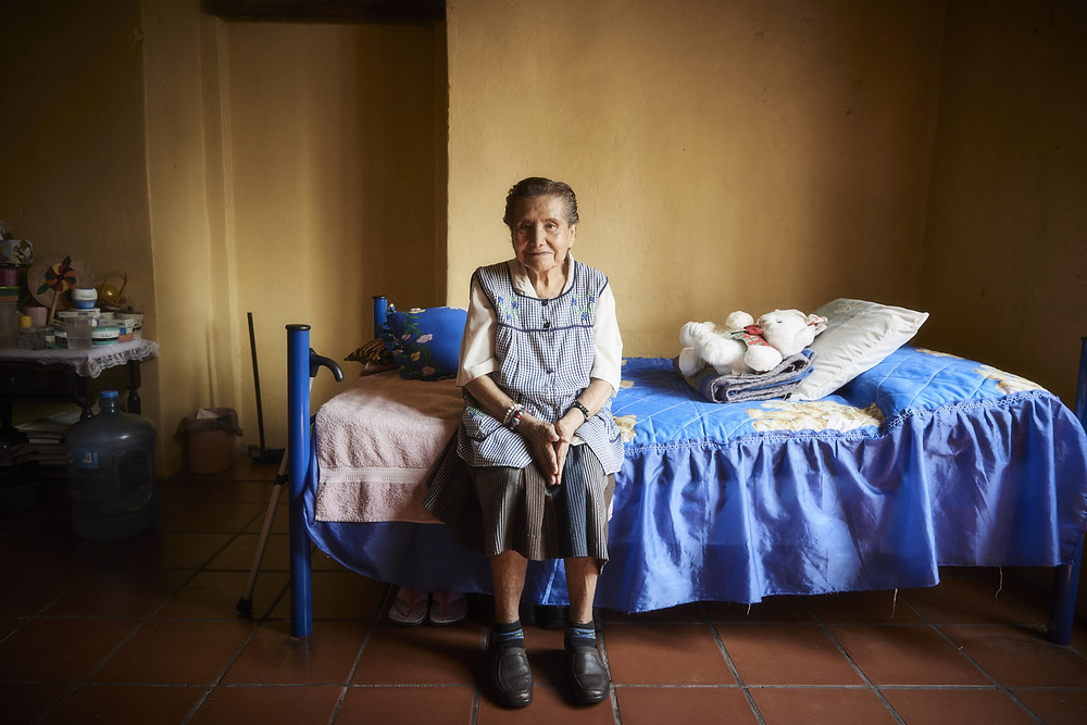 Normita, aged 82, sits on her bed where her stuffed teddy bear also rests in her bedroom in Casa Xochiquetzal, Mexico City, June 2016. From the series 'Casa Xochiquetzal', a personal project. Shot in Mexico City, June 2017.