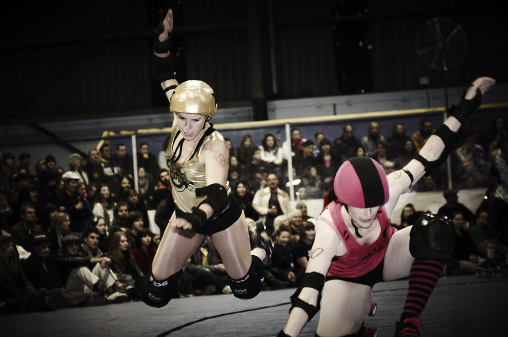 Two Roller Derby girls fly through the air as they crash into each other during a bout. From the series 'Derby Girls', shot for the Big Issue in January 2011.