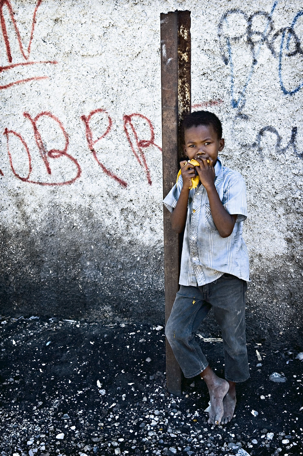 A street boy eats a mango. From the series 'The Haiti Project' a personal project shot in Cite Soleil, Haiti, March 2006.