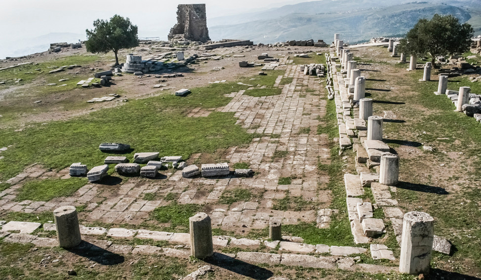 Tiled patio of the sanctuary of Athena and adjacent Stoas. In the background the remains of the temple of Athena and the byzantine tower erected in  twelfth century as a watchtower.