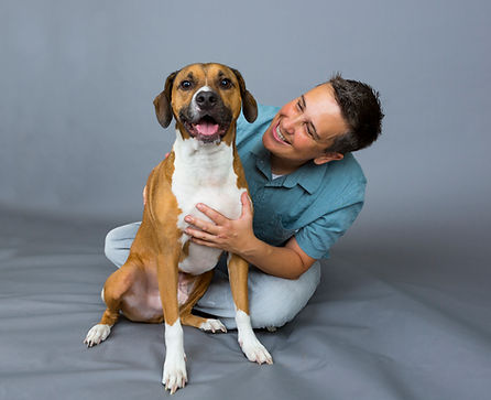 Shane and the Mighty Mutts logo hound dog, Watson, sit on the floor. Human and dog are smiling.