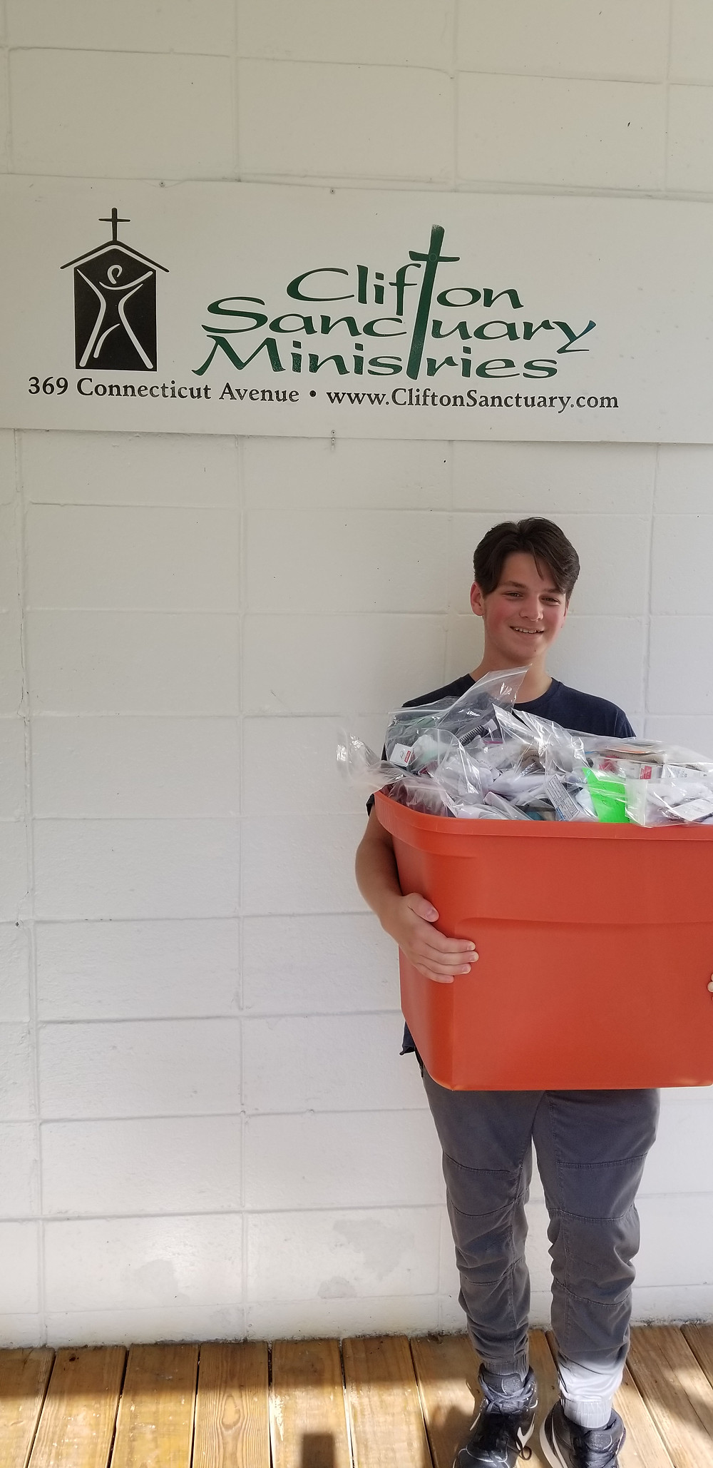 Young person bringing hygiene kits to the guests at Clifton Sanctuary Ministries Atlanta homeless shelter for men