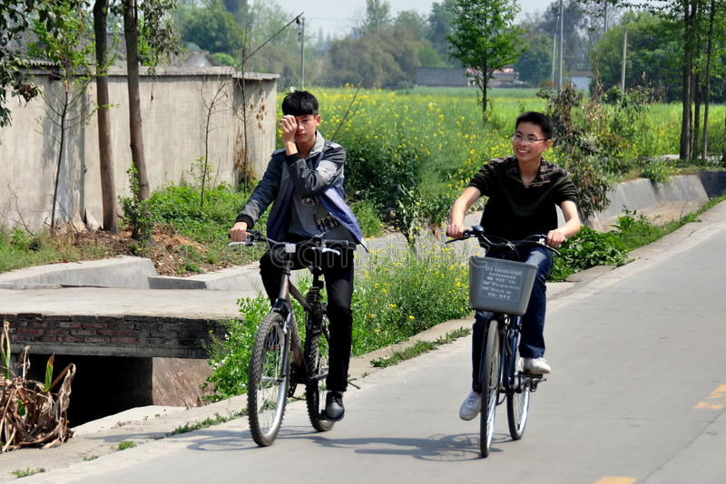 deux-adolescents-chinois-montant-leurs-bicyclettes-le-long-d-une-route-de-campagne-pittoresque-provi