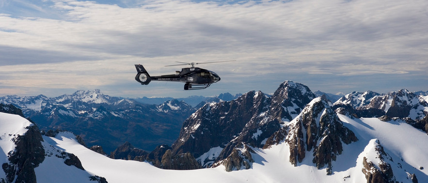 Helicopter Ride Over Snowcovered Mountains