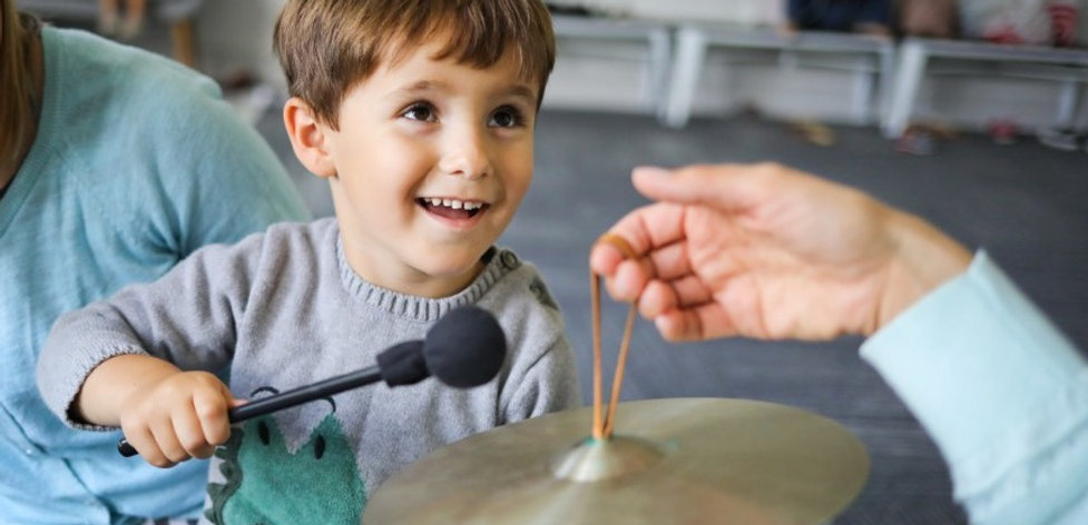 toddler playing cymbal