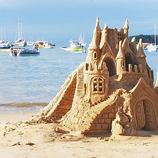 tall-sand-castle-on-beach-with-boats-in-