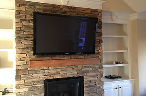 Meadowlands Golf TV mounted on stone fireplace