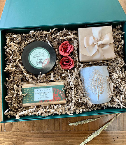 Gift set for a garden person with soaps, hand balms, a luxury candle in a ceramic pot and chocolate truflles