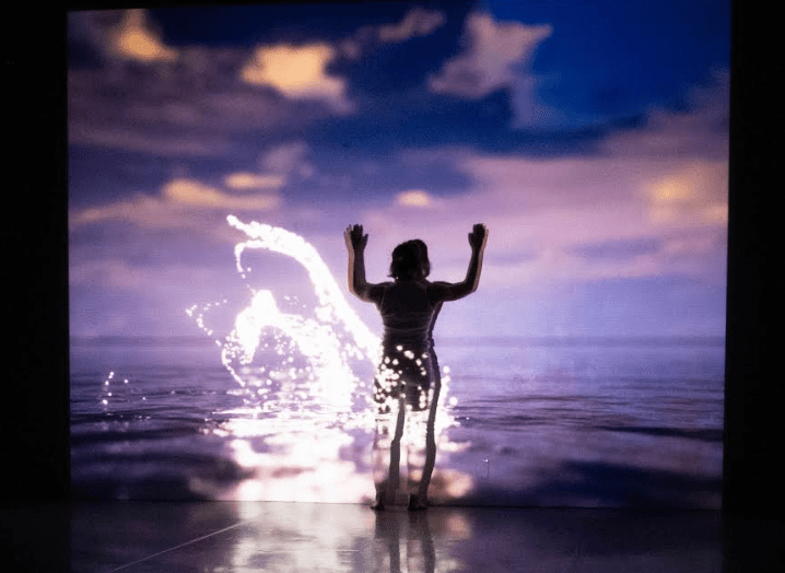 Dancer Kara Beadle silhouetted in front of a projection of splashing waves.