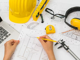 hand-construction-plans-with-yellow-helm