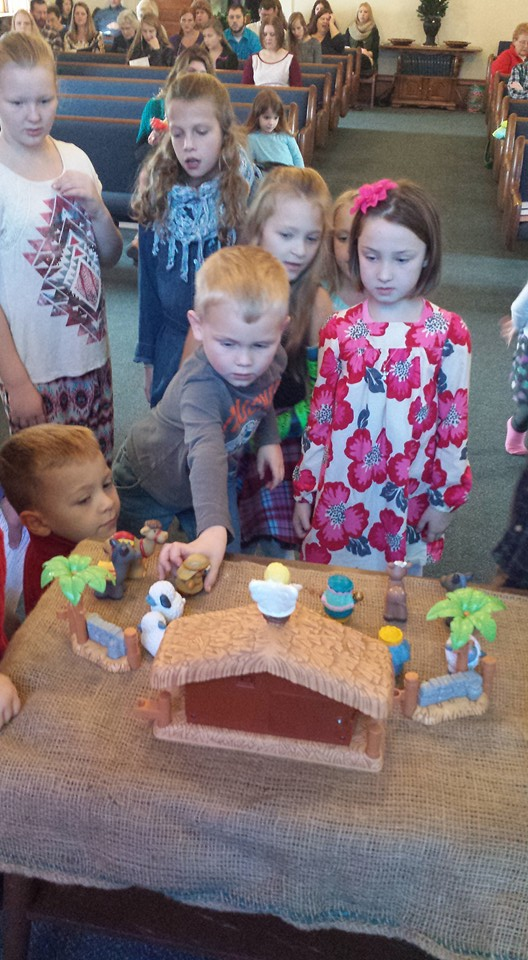 Children set up the nativity scene
