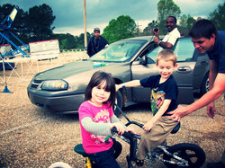 2 young children enjoy a bike ride